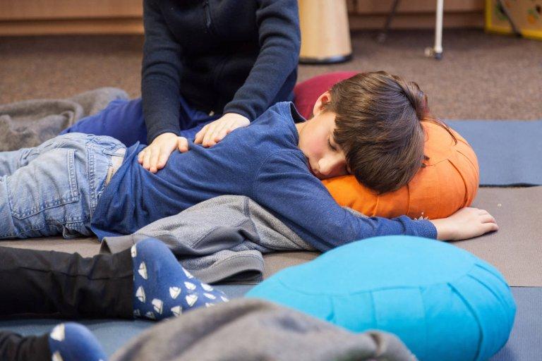 Ein auf dem Boden liegendes Kind mit geschlossenen Augen, auf seinem Rücken ruhen die Hände eines anderen Kindes