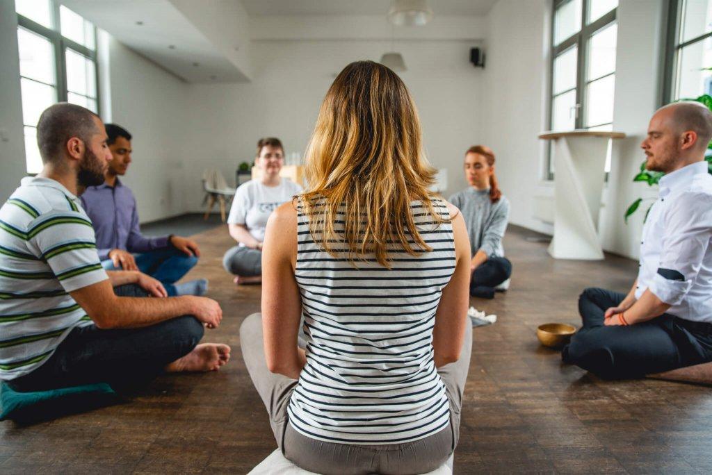 Im Kreis auf dem Boden sitzende Personen bei der Meditation