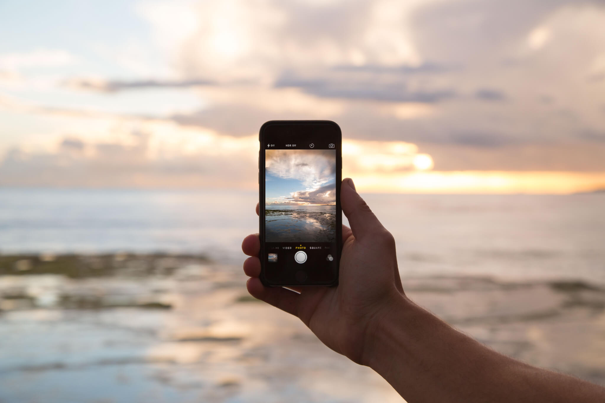 a hand holding a smartphone taking a picture of the sea