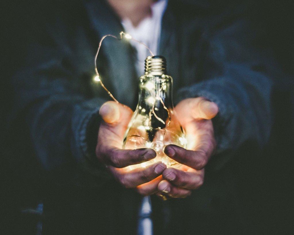 Eine Person hält eine Glühbirne in den Händen